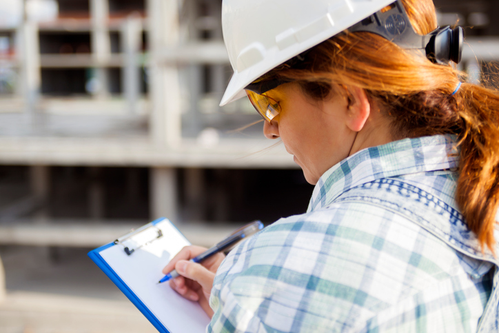 Female architect writing on clipboard and keeping good records on construction projects