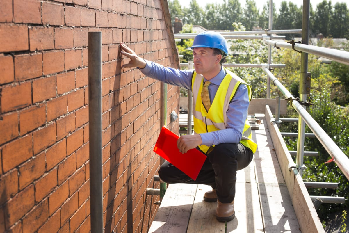 Builder assesses brickwork on a gable end. Estimating estimator