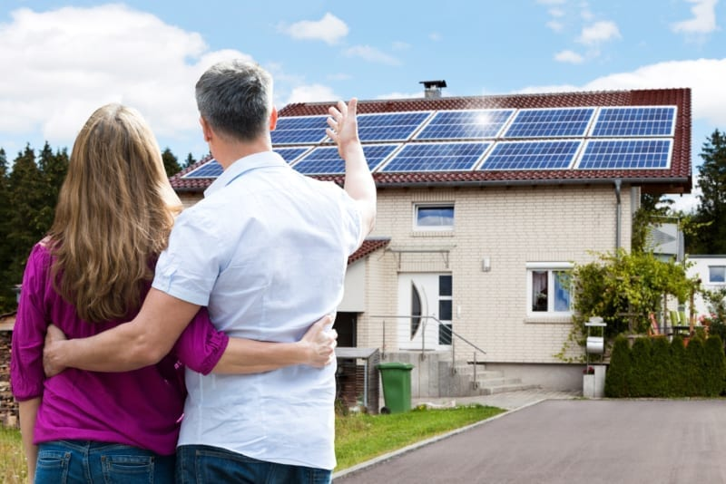 Rear View Of Couple Standing In Front Of Their net-zero House