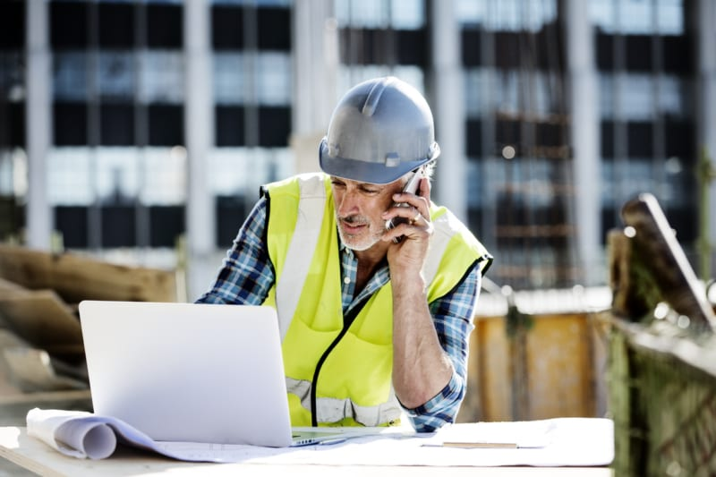 Male architect using mobile phone and laptop at construction site