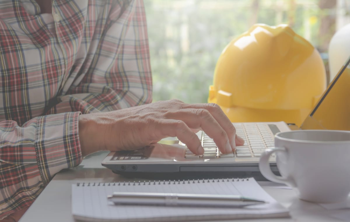 Contractor working with yellow helmet, laptop and coffee cup on table.