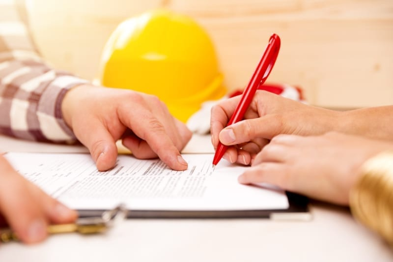 Woman signing construction contract with contractor to build a house