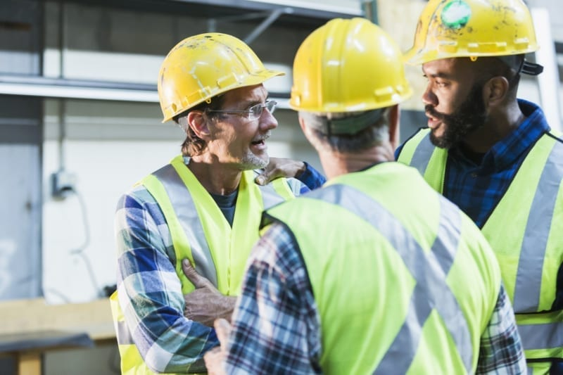 A group of three multi-ethnic men wearing hard hats and safety vests having a meeting. They are serious expressions on their faces, perhaps having a disagreement. The focus is on the two men in the background.
