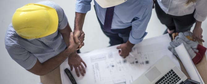 Team of one women architect and two men architects on a construction site. Men are shaking hands on a construction contract