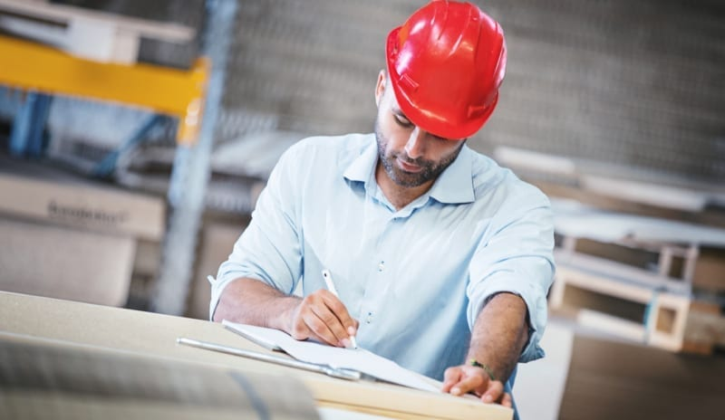 Closeup front view of mid 30's wood processing entrepreneur performing a weekly warehouse inspection of a wood working factory. He's counting items in the storage and writing it in his notepad. He's wearing light blue shirt and red helmet.